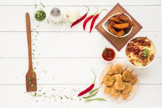 Telaio composto da oggetti da cucina, spezie, verdure e farina di carne di pollo Foto Gratuite