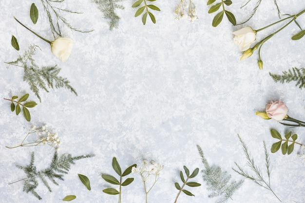 Telaio da fiori di rosa e rami di piante sul tavolo Foto Gratuite