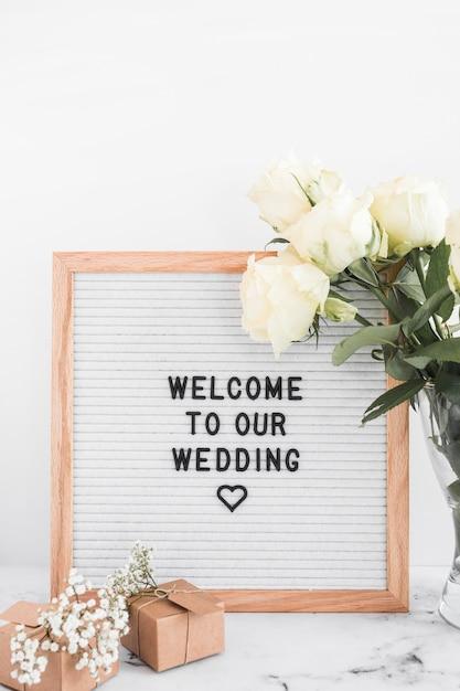 Telaio di benvenuto per il matrimonio con scatole regalo e rose su sfondo bianco Foto Gratuite