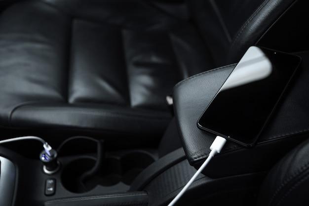 Telefono cellulare, batteria di ricarica per smartphone, ricarica nella presa per auto da vicino Foto Premium