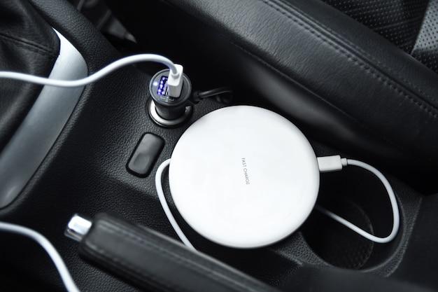 Telefono cellulare, batteria di ricarica per smartphone, ricarica wireless nella presa per auto da vicino Foto Premium