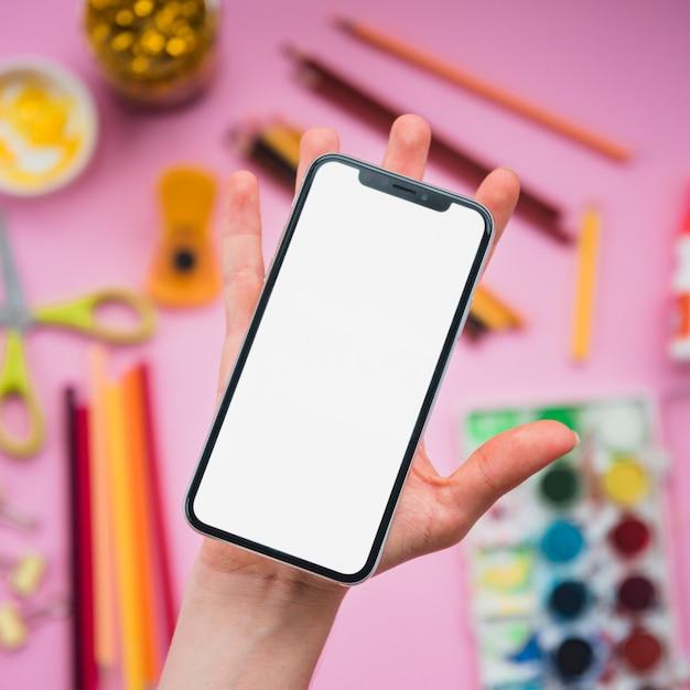 Telefono cellulare con schermo bianco vuoto sulla palma umana sopra stationer offuscata a sfondo Foto Gratuite