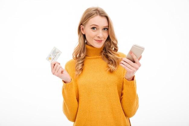 Telefono cellulare e carta di credito sorridenti della tenuta della giovane donna. Foto Gratuite