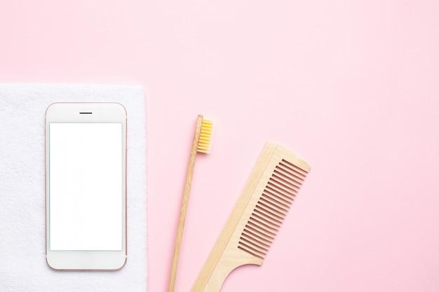 Telefono cellulare e spazzolino da denti in legno eco, pettine, spazzola per massaggio a secco su rosa Foto Premium