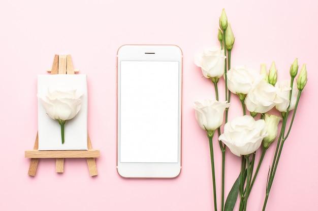 Telefono cellulare e tela per pittura con fiore bianco su rosa Foto Premium