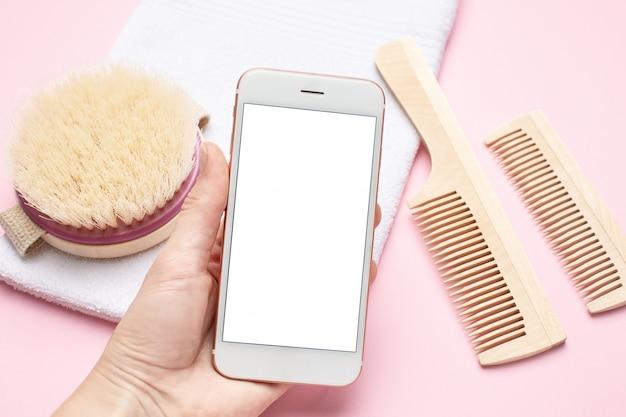 Telefono cellulare in mano ed eco spazzolino da denti in legno, pettine, spazzola per massaggio a secco su rosa Foto Premium