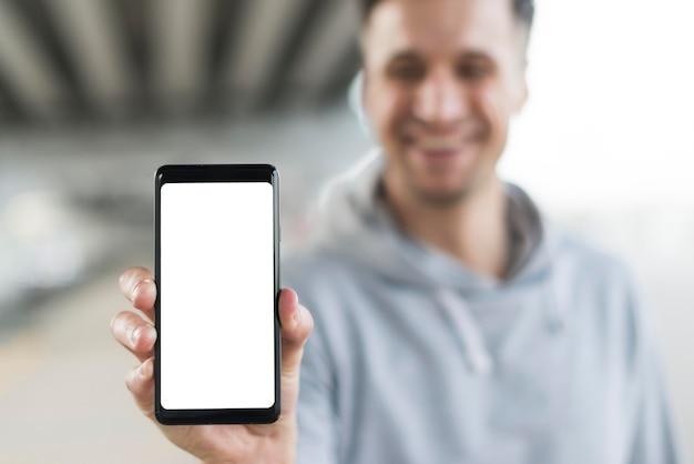 Telefono cellulare maschio della tenuta del primo piano Foto Gratuite