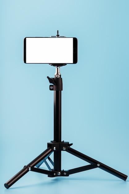 Telefono cellulare montato su un treppiede con display bianco gratuito per immagini e testo, sfondo blu isolato. Foto Premium
