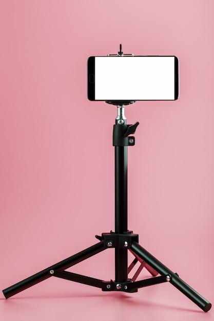 Telefono cellulare montato su un treppiede con display bianco gratuito per immagini e testo, sfondo rosa isolato. Foto Premium