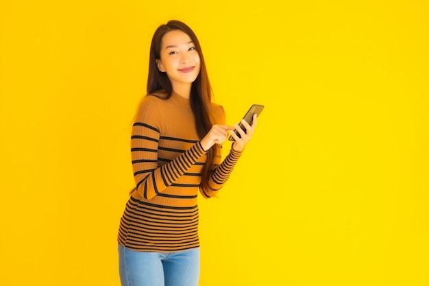 Telefono cellulare o cellulare astuto di bello giovane uso asiatico della donna con molta azione su fondo giallo Foto Gratuite