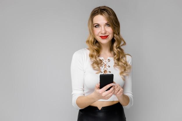 Telefono cellulare sorridente della tenuta dei giovani vestiti biondi attraenti della donna di affari in bianco e nero in sue mani che stanno nell'ufficio su fondo grigio Foto Premium