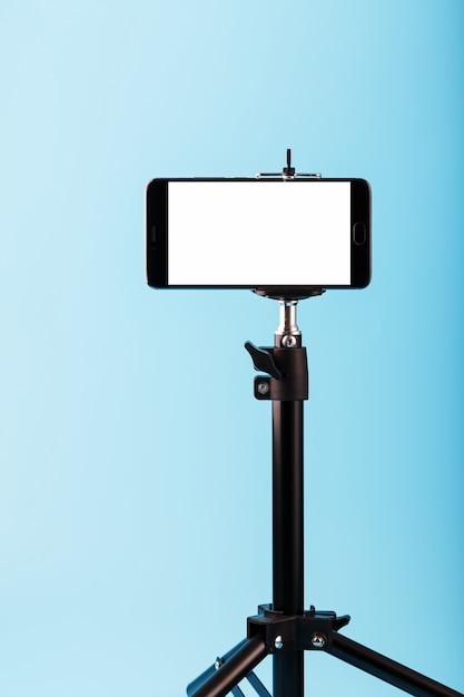 Telefono cellulare su un treppiede con un display bianco chiaro per immagine e testo, sfondo blu isolato. Foto Premium