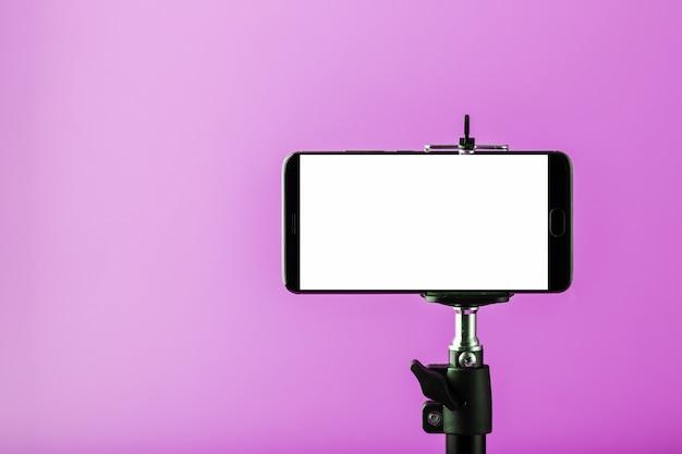 Telefono cellulare su un treppiede con un display bianco chiaro per immagini e testo, sfondo rosa isolato. Foto Premium