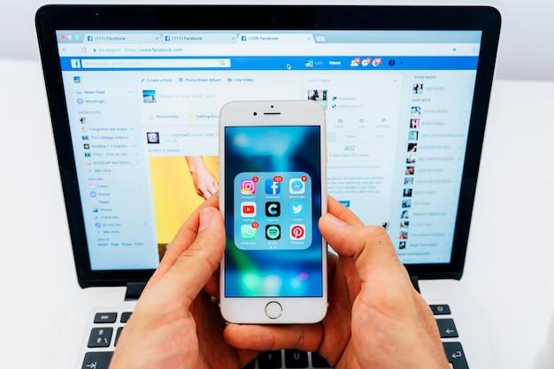 Telefono con applicazioni e computer portatile con facebook Foto Gratuite