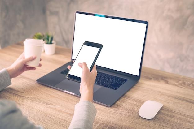 Telefono della tenuta della donna dei pantaloni a vita bassa e computer portatile usando sul tavolo di legno nella caffetteria. Foto Premium