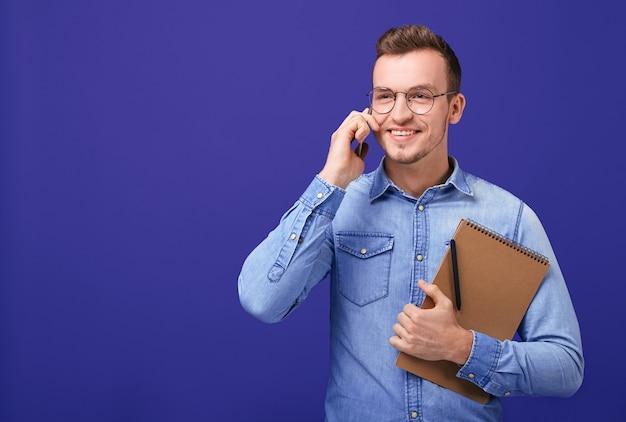 Telefono parlante dell'uomo d'affari bello pensieroso con il taccuino a disposizione Foto Premium