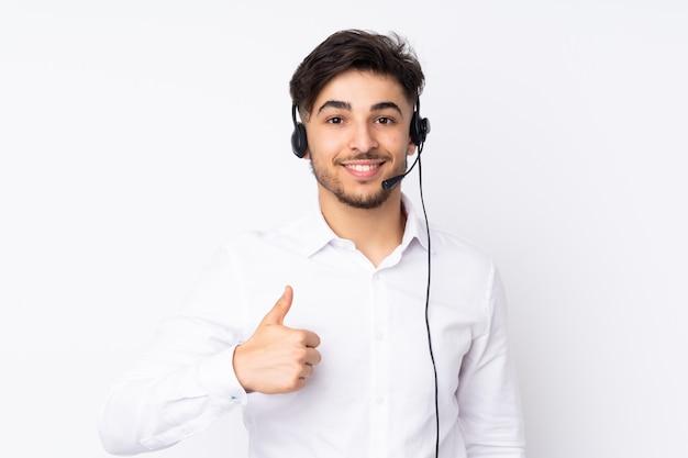 Telemarketer lavorando con un auricolare isolato sul muro bianco dando un pollice in alto gesto Foto Premium
