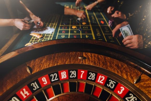 Tema del casinò. giocatori irriconoscibili giocano al casinò con denaro. Foto Premium