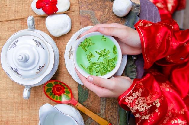 Tempo cinese del tè di festival di luna. vista superiore sulle mani della donna con la tazza di tè verde in traditiona Foto Premium