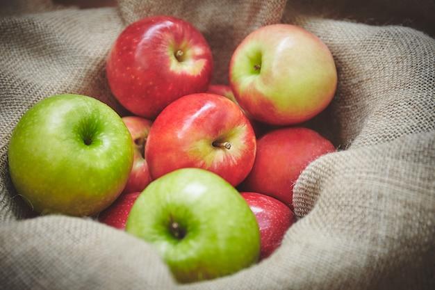 Tempo di raccolta, mele delle materie organiche dalla merce nel carrello della natura su struttura del fondo della tela di sacco Foto Premium