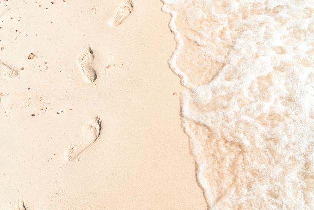 Tempo libero in estate - orme su sabbia con onde marine. effetto colore vintage. Foto Premium