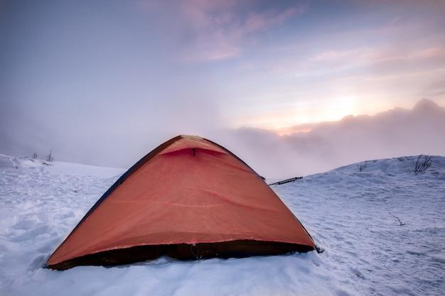 Tenda arancione di campeggio sulla collina nevosa in mattinata Foto Premium
