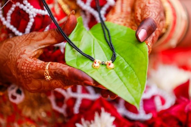 Tenendo i mangalsutra sulla mano della sposa il simbolo del matrimonio nell'induismo Foto Premium