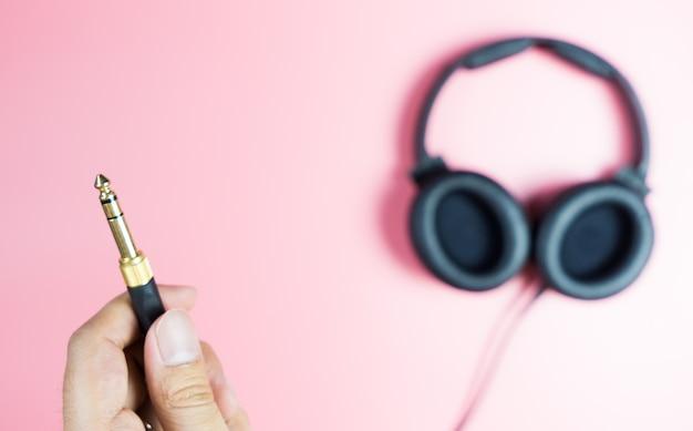 Tenendo il jack per cuffie d'oro su sfondo rosa Foto Premium