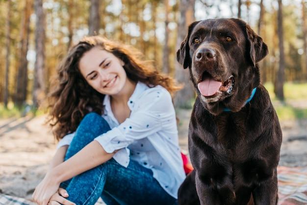 Tenera scena di ragazza felice con il suo animale domestico nella foresta Foto Gratuite