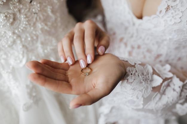 Tenero anello di fidanzamento dorato con diamante sulla mano della donna con manicure e abito da sposa decollete Foto Gratuite