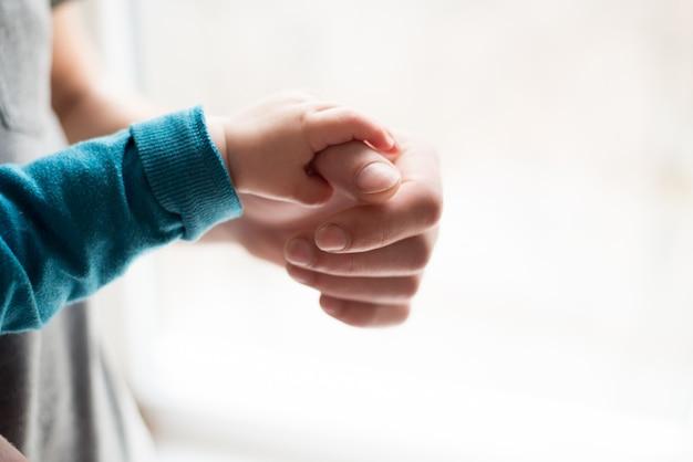 Tenersi per mano. mano il bambino addormentato nella mano del primo piano di padre. mani isolate su sfondo bianco Foto Premium