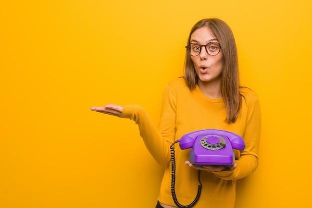 Tenuta abbastanza giovane della donna caucasica qualcosa sulla mano della palma. lei è in possesso di un telefono vintage. Foto Premium