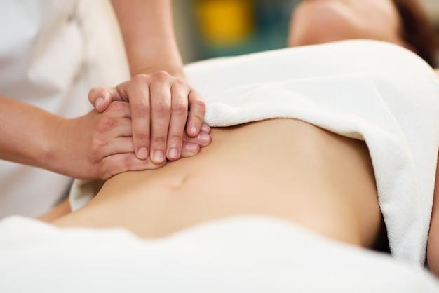 Terapista che applica pressione sulla pancia. mani che massaggiano l'addome della donna. Foto Premium