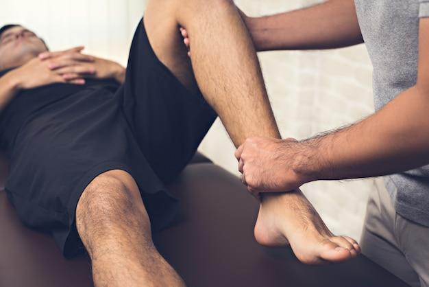 Terapista che cura gamba ferita del paziente maschio dell'atleta in clinica Foto Premium