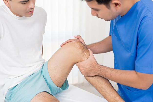 Terapista che cura ginocchio ferito del paziente maschio in ospedale Foto Premium