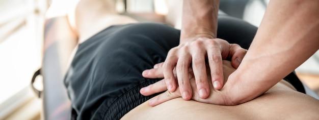 Terapista che dà massaggio della parte posteriore della parte inferiore al paziente maschio dell'atleta Foto Premium