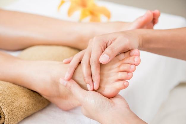 Terapista che dà rilassante massaggio riflessologico tradizionale ai piedi di una donna nella spa Foto Premium