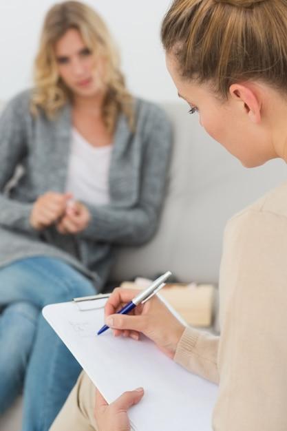 Terapista che scrive le note sui suoi appunti Foto Premium