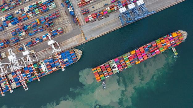 Terminale della nave da carico di vista aerea, gru di scarico del terminale della nave da carico, porto industriale di vista aerea con i contenitori. Foto Premium
