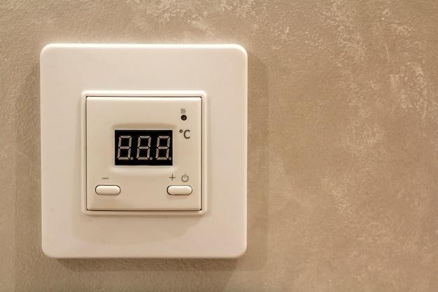 Termostato digitale programmabile elettronico bianco sul fondo leggero dello spazio della copia della parete. controllo del clima, temperatura domestica confortevole, concetto di risparmio energetico. Foto Premium