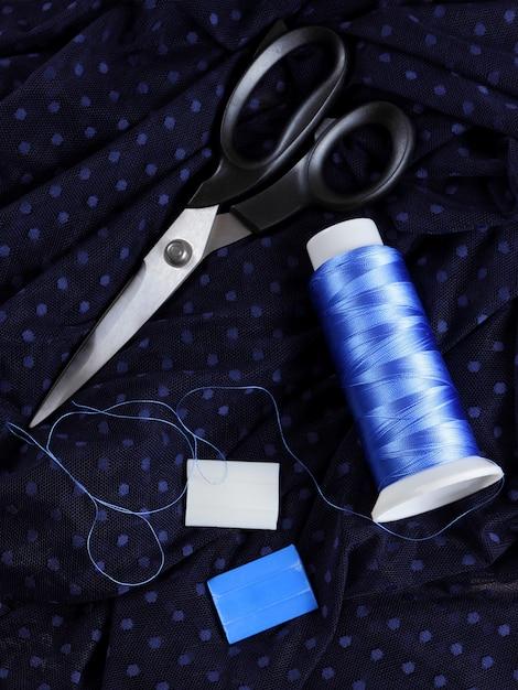 Tessuto scuro con pois e filo di seta blu. processo di sartoria. forbici e rocchetto di filo su tessuto nero. Foto Premium