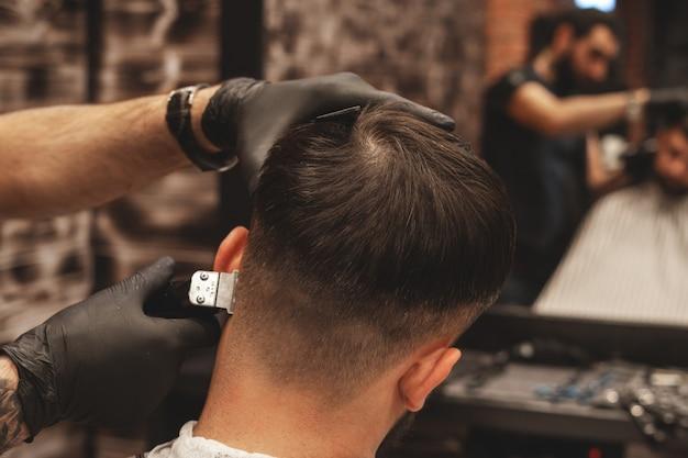 Testa di taglio di capelli nel barbiere. il barbiere taglia i capelli sulla testa del cliente. il processo di creazione di acconciature per uomo. barbiere. messa a fuoco selettiva. Foto Premium