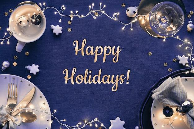 Testo buone vacanze. allestimento tavola natalizia con piatti bianchi, utensili dorati e decorazioni dorate rosso scuro. vista piana laico e dall'alto su tessuto di lino blu scuro. Foto Premium