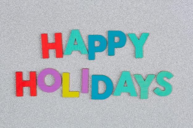 Testo colorato buone feste organizzato con lettere su glitter argento Foto Premium