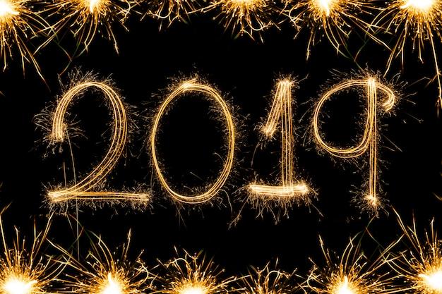 Testo del buon anno 2018 scritto con i fuochi d'artificio della scintilla isolati su fondo nero Foto Premium