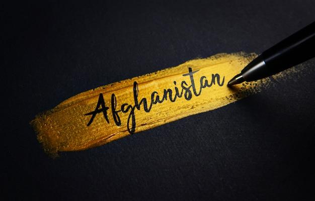 Testo della grafia dell'afghanistan sul tratto di pennello dorato Foto Premium