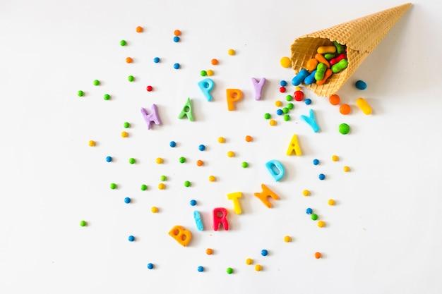 Testo di giorno di nascita felice con caramelle che si rovesciano dal cono gelato della cialda Foto Gratuite