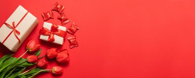 Testo di happy mothers day e bei tulipani rossi con confezione regalo su sfondo rosso. cartolina d'auguri felice di festa della mamma con i fiori di primavera. Foto Premium