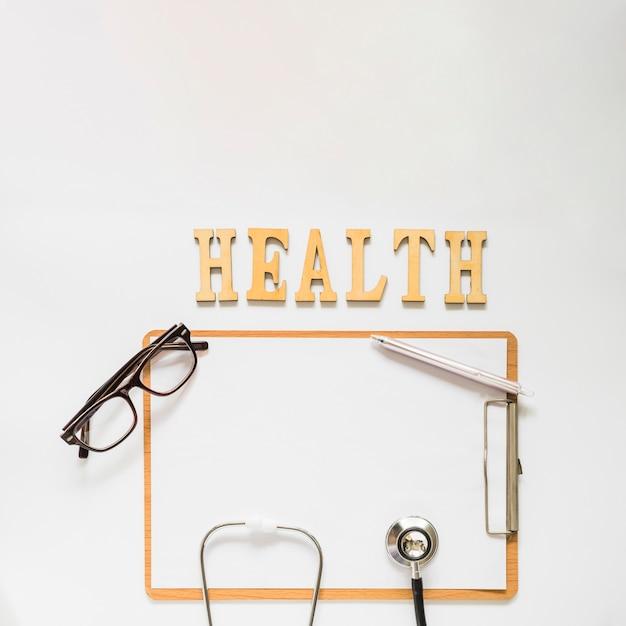 Testo di salute vicino agli appunti con gli occhiali; stetoscopio e penna su sfondo bianco Foto Gratuite