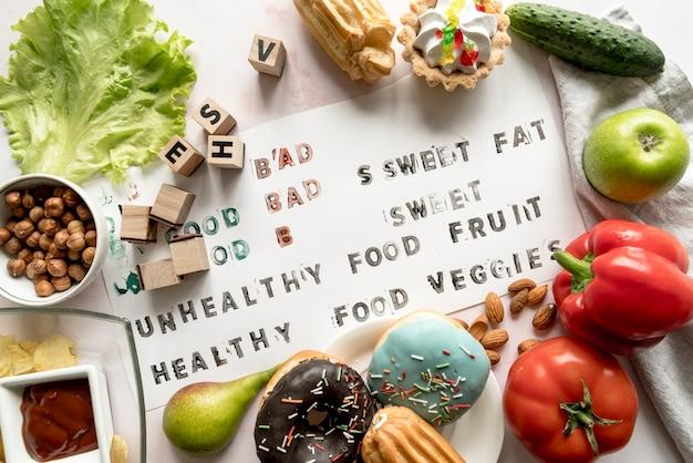 Testo sano e malsano su carta circondato con cibo fresco Foto Gratuite